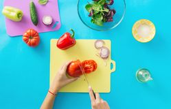 Female hands prepare summer vegetarian salad Healthy food Diet f. Female hands prepare summer vegetarian salad on blue background. Healthy food konept. Diet food Stock Photo