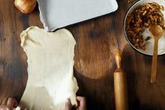 Female hands preparing apple pie strudel wooden table top view. Female hands preparing apple pie or strudel on wooden table, top view royalty free stock photography