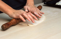 Female hands preparing dough with rolling pin Stock Images