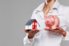 Female hands presenting a piggy bank and a model house Stock Image