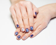 Female hands with professional blue and silver manicure. Close up of female hands with professional blue and silver manicure isolated on white background. Art stock images