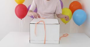 Female hands pulling a red ribbon to open gift box. In a blue box stock video
