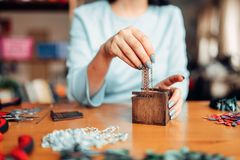 Female hands pulls out metal chain from box. Female person hands pulls out a metal chain from a wooden box, master at work. Handmade jewelry. Needlework Royalty Free Stock Images