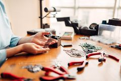 Female hands pulls out metal chain from box. Female person hands pulls out a metal chain from a wooden box, master at work. Handmade jewelry. Needlework Stock Images