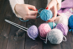 Female hands with purple manicure are knitted metal spokes of a Royalty Free Stock Image