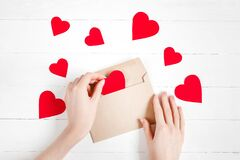 Free Female Hands Put Red Hearts In A Congratulatory Envelope On A White Wooden Background  Happy Valentine`s Day Background  Love Royalty Free Stock Image - 209103336