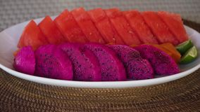 Plate with ripe tropical fruits. Female hands put on the table Assorted fresh ripe tropical fruits on a plate including Dragon fruit,pitaya, watermelon. Fresh stock video