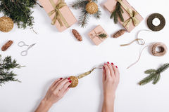 Female hands put yellow Christmas ball on a white table with bra Royalty Free Stock Photography