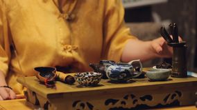 Female hands putting herbal leaves in teapot, performing history art traditions. Stock footage stock video
