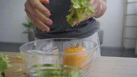 Female hands putting lettuce in the deep bowl. Unrecognizable woman cooking breakfast in the kitchen. Healthy lifestyle. Female hands putting lettuce in the deep stock footage
