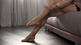 Female hands putting on nylon tights in bedroom, getting ready for night party stock images