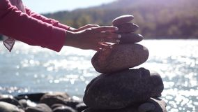 Female hands putting pebble stack next to the mountain river on sunny day Royalty Free Stock Photo