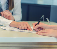 Female hands putting signature to agreement royalty free stock images