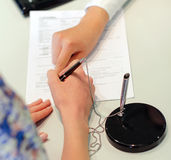 Female hands putting signature to agreement Royalty Free Stock Photo