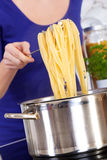 Female hands raising cooked pasta out of the pot Stock Photo