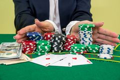 Female hands reaching for poker chips, play card. In casino stock image