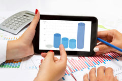 Female hands reading business columns on tablet, at office desk. Stock Photos
