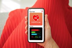 Female hands red dress holding phone app heart and activity. Female hands in red dress holding phone with app heart and activity on the screen royalty free stock photography