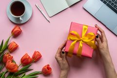 Female hands with red gift box on pink background. Background with coffee, laptop and flowers. stock images