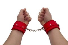 Female hands in red leather handcuffs. royalty free stock image