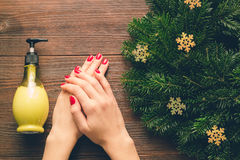 Female hands with red manicure and a bottle of hand cream on a w Stock Image