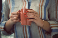 Female hands with red manicure holding coffee cup Royalty Free Stock Image