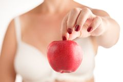 Female hands with red manicure holding a red and yellow apple on Royalty Free Stock Images
