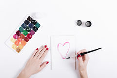 Female hands with red manicure painted watercolor heart in a not. Ebook, top view stock photography