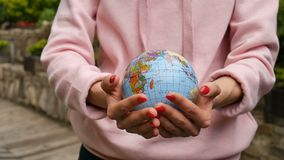 Female hands with red manicure taking a small globe with geografical names in Ukrainian cyrillic letters on it. Human. Responsibility concept, HD stock footage