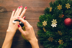 Female hands with red nail Polish applied hand cream Stock Photography