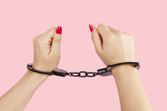 Female hands with red nails in handcuffs. Stock Photo