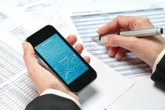 Female hands reviewing accounting on smart phone. Royalty Free Stock Photo