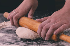 Female hands roll out pastry with rolling-pin Stock Photo