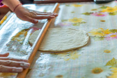 Female hands rolling raw dough on white table. At home Stock Photos
