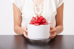 Female hands and round gift box on the table Royalty Free Stock Images