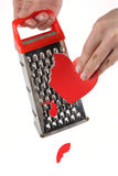 Female hands rubbing heart on a kitchen grater Stock Photo