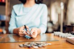 Female hands with scissors, handmade jewelry. Female person hands with scissors, handmade jewelry. Needlework, bijouterie making Stock Photography