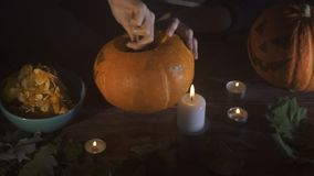 Female hands scooping out seeds and contents of pumpkin on wooden table with candles at night. Halloween theme, jack stock footage