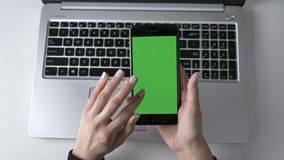 Female hands scrolling on the smartphone`s touchscreen. Green screen, chromakey concept, laptop in the background. Top. Shot 60 fps 4k stock footage