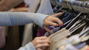 Female hands selecting colorful clothes on hangers stock video footage