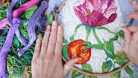 Female hands setting embroidery hoop for needlework. Flat lay, top view. Hobby