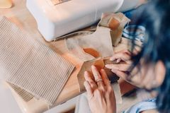 Female hands sewing fabric with needle at seamstress workplace of sewing process. Hands stitching fabric on  machine hobby at home. blurred background royalty free stock photography