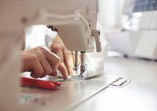 Female hands at sewing process and repairing white fabric on professional manufacturing machine. Front close up view. Woman hands stitching white fabric on royalty free stock images