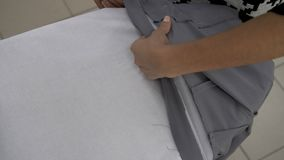 Female hands are sewn with a tailor`s iron gray cloth for further work with her stock video