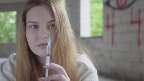 Woman shake off heroin from a syringe preparing to make injection close up. Addiction to drugs. Unhealthy lifestyle, bad. Female hands shake off heroin from stock video footage