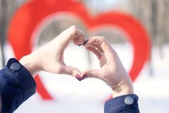 Female hands in the shape of heart against the background of big red heart street installation in winter park. Love, romance,. Valentine& x27;s Day concept royalty free stock image