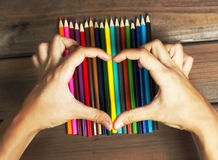 Female hands in the shape of a heart on colored pencils on a bac Stock Image