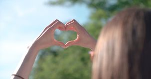 Female hands in shape of heart over green nature and blue sky. Royalty Free Stock Photography