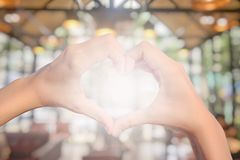 Female hands in shape of love heart on bokeh. Background royalty free stock photography