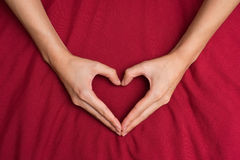 Female hands shaping a heart red background 1 Royalty Free Stock Photo